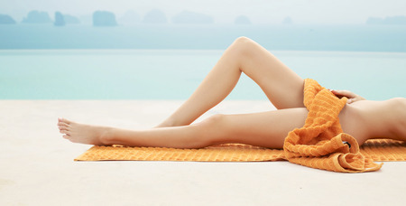 people, summer, beauty and vacation concept - close up of woman legs with orange towel at resort beach or pool photo