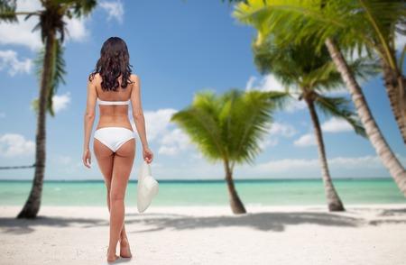 人々、旅行、水着、夏、美容コンセプト - ヤシの木の背景を持つ熱帯のビーチを後ろから白いビキニ水着の若い女性