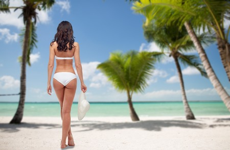 people, travel, swimwear, summer and beauty concept - young woman in white bikini swimsuit from back over tropical beach with palm trees background Stock Photo
