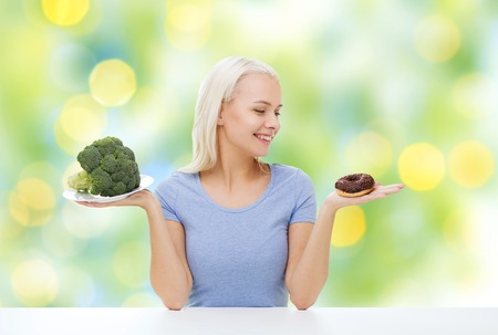summer diet: healthy eating, junk food, diet and choice people concept - smiling woman choosing between broccoli and donut over summer green holidays lights background