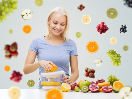 comidas saludables: una alimentaci�n sana, comida vegetariana, la dieta, la desintoxicaci�n y la gente concepto - mujer con el exprimidor exprimir el jugo de fruta sobre frutas y bayas en el fondo gris sonriendo