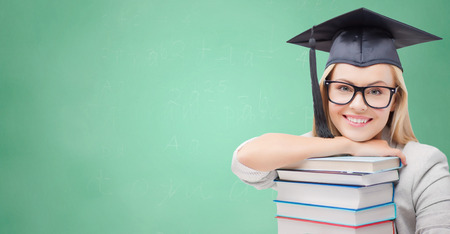 trencher: education, high school, knowledge, and people concept - picture of happy student girl or woman in trencher cap with stack of books over green chalk board background Stock Photo