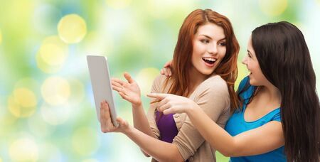 women friendship: technology, friendship and people concept - two smiling teenage girls or young women pointing finger at tablet pc computer over green lights background
