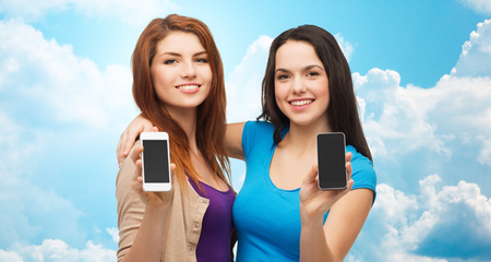 showing: advertisement, cloud computing, people and modern technology concept - two smiling teenage girls or young women showing blank smartphones screens over blue sky with clouds background Stock Photo