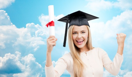 trencher: education, high school, knowledge, graduation and people concept - happy student girl or woman in trencher cap with diploma certificate over blue sky and clouds background