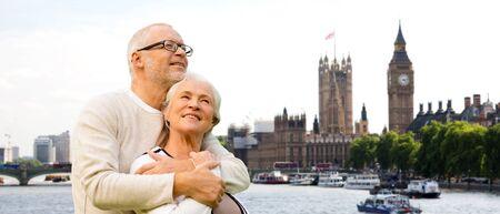 viaje familia: familiar, la edad, el turismo, los viajes y el concepto de la gente - par mayor feliz sobre las casas del parlamento o del palacio de Westminster y la torre del reloj Big Ben en Londres Foto de archivo