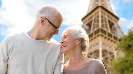 family, age, tourism, travel and people concept - happy senior couple over paris eiffel tower in france Stock Photo