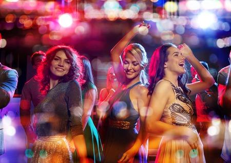 fiesta, días de fiesta, celebración, vida nocturna y el concepto de la gente - amigos felices bailando en el club con las vacaciones luces