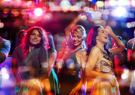 party friends: party, holidays, celebration, nightlife and people concept - happy friends dancing in club with holidays lights Stock Photo