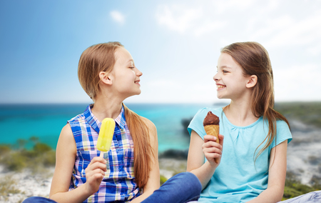 preteen girl: people, children, friends and friendship concept - happy little girls eating ice-cream over summer beach background