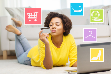 personas, banco por Internet, compras en línea, la tecnología y el concepto de dinero electrónico - feliz mujer joven afroamericana tirado en el suelo con el ordenador portátil y una tarjeta de crédito en casa encima de los iconos de Internet