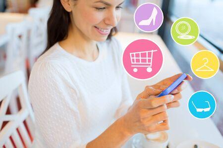 chicas de compras: la gente, compras en línea, la tecnología y el concepto de estilo de vida - mujer joven sonriente con teléfonos inteligentes y los iconos de Internet en el café