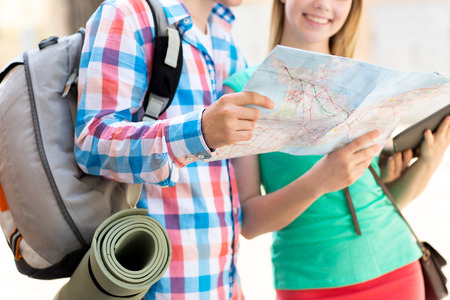 travel, tourism, summer vacation and people concept - smiling couple with map, tablet pc computer and backpack in city