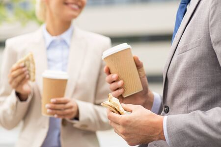 man drinking coffee: business, food, drink, communication and people concept - close up of smiling businessmen with coffee cups and sandwiches having lunch and talking outdoors
