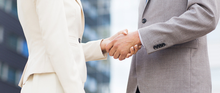 young entrepreneurs: business, partnership, success, gesture and people concept - close up of business couple shaking hands on city street over office building