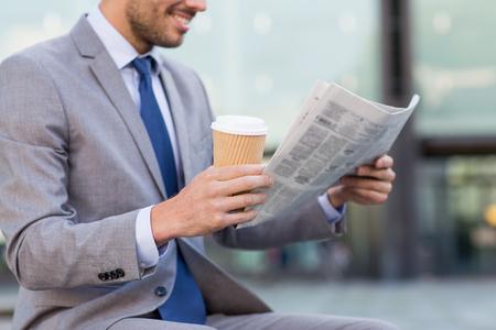 biznes, wiadomości, złamać, a ludzie i pojęcie - zamknąć się uśmiechnięta biznesmen czyta gazetę i pijąc kawę z papierowego kubka nad budynkiem biurowym