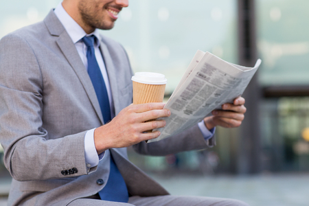 business, news, break and people and concept - close up of smiling businessman reading newspaper and drinking coffee from paper cup over office building