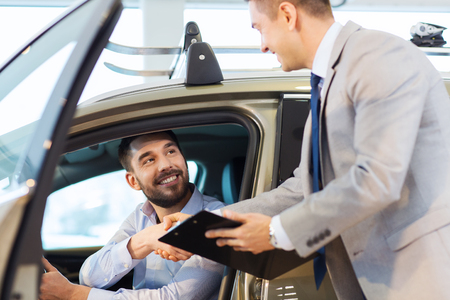 car service: auto business, car sale, consumerism, gesture and people concept - happy man with car dealer making deal and shaking hands in auto show or salon