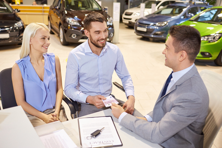 automobile dealer: auto business, sale and people concept - happy couple with dealer buying car in auto show or salon