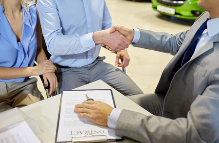 auto business, car sale, gesture and people concept - close up of customers couple with dealer shaking hands in auto show or salon