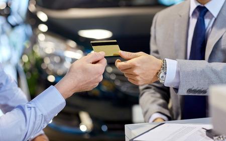 auto handel, verkoop en mensen concept - close-up van de klant die creditcard geeft aan autohandelaar in autoshow of salon