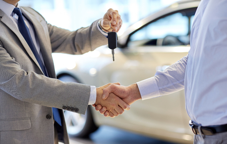 auto business, car sale, deal, gesture and people concept - close up of dealer giving key to new owner and shaking hands in auto show or salon Standard-Bild