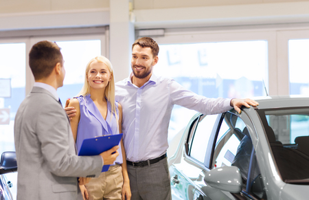 used: auto business, car sale, technology and people concept - happy couple with car dealer in auto show or salon