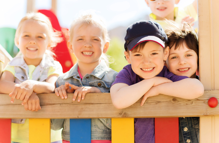 kids outside: summer, childhood, leisure, friendship and people concept - group of happy kids on children playground
