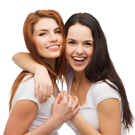 friendship and happy people concept - two laughing girls in white t-shirt hugging Stock Photo