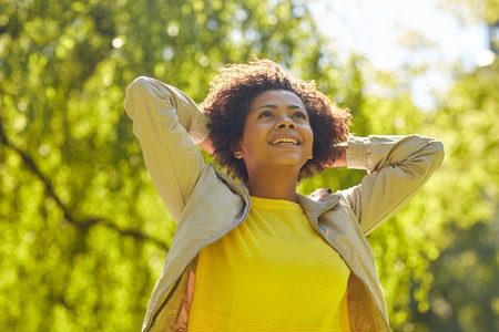 mensen, ras, etniciteit en portretconcept - gelukkige Afrikaanse Amerikaanse jonge vrouw in de zomerpark Stockfoto