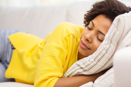 people, rest, comfort and leisure concept - african american young woman sleeping on sofa at home Stock Photo
