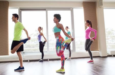 estiramientos: fitness, deporte, entrenamiento, gimnasio y el concepto de estilo de vida - grupo de gente sonriente con el entrenador el ejercicio de estiramiento en el gimnasio