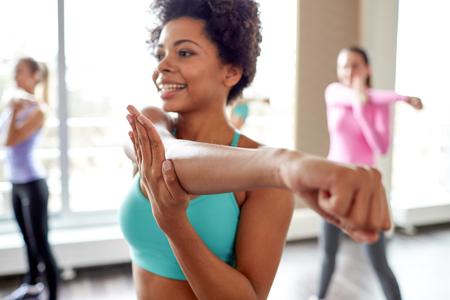 фитнес: фитнес, спорт, танцы, люди и образ жизни концепция - закрыть улыбается афро-американских женщин с группой женщин, танцующих Zumba в тренажерном зале или студии