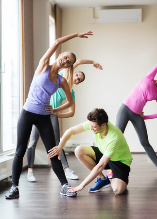 Fitness, Sport, Training, Fitness-Studio und Lifestyle-Konzept - Gruppe von lächelnden Menschen in der Turnhalle Stretching