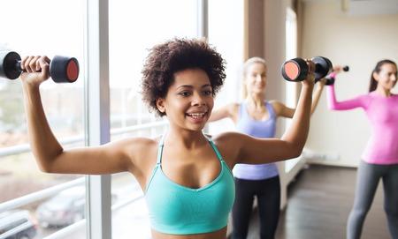 mujeres africanas: fitness, deporte, entrenamiento y estilo de vida concepto - grupo de mujeres felices con pesas flexionar los músculos en el gimnasio Foto de archivo