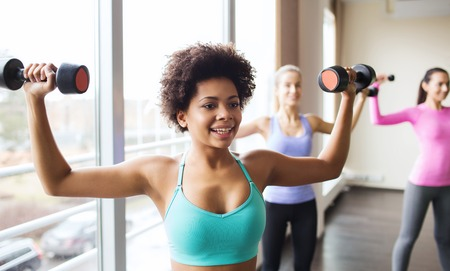 african woman: fitness, sport, training and lifestyle concept - group of happy women with dumbbells flexing muscles in gym