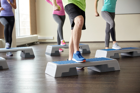 step fitness: fitness, sport, aerobics and people concept - group of smiling people working out and flexing legs on step platforms in gym