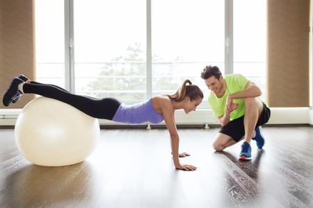 ENTRENANDO: deporte, fitness, estilo de vida y concepto de la gente - la sonrisa del hombre y de la mujer con bola de ejercicio en el gimnasio Foto de archivo
