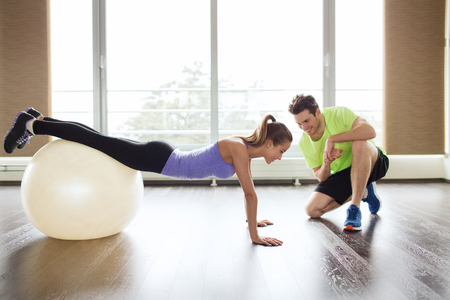 sport, fitness, lifestyle and people concept - smiling man and woman working out with exercise ball in gym Stock Photo