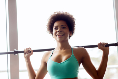 fitness, sport, training and people concept - happy smiling african american woman holding bar in gym Stock Photo