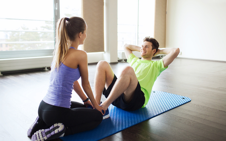 personal trainer: fitness, sport, training, teamwork and people concept - woman with personal trainer doing sit ups in gym Stock Photo