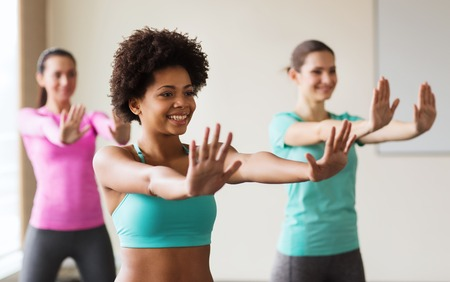 zumba: fitness, sport, dance and lifestyle concept - group of smiling people with coach dancing zumba in gym or studio