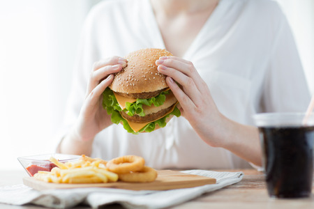 패스트 푸드, 사람과 건강에 해로운 먹는 개념은 - 가까운 여자 손의 닫 햄버거 또는 치즈 버거를 들고 스톡 콘텐츠