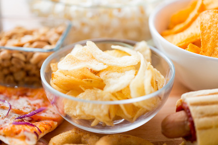 ファーストフード、ジャンク フード、料理、食事の概念 - は、ガラスのボウル、その他軽食でカリカリ ポテト ポテトチップスのクローズ アップ