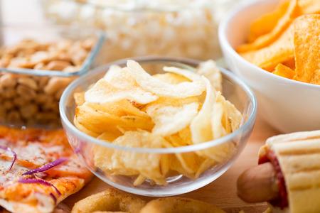 comida chatarra: comida rápida, comida basura, la gastronomía y Concepto de alimentación - cerca de las patatas fritas crujientes en un tazón de vidrio y otros aperitivos