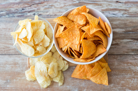 potato crisps: fast food, junk-food, cuisine and eating concept - close up of potato crisps and corn nachos in bowls on table Stock Photo