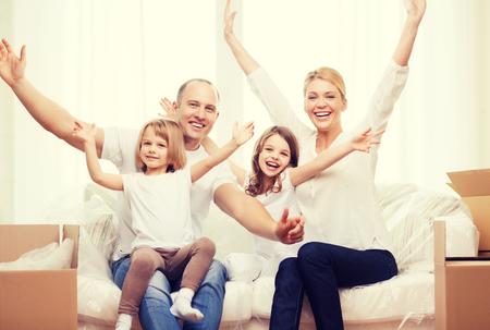 la familia, los niños, el alojamiento y el concepto de casa - los padres sonrientes y dos niñas pequeñas que agitan las manos en el nuevo hogar