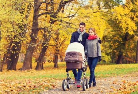 autumn young: love, parenthood, family, season and people concept - smiling couple with baby pram in autumn park