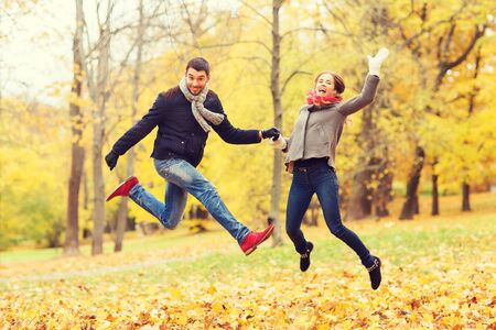 autumn young: love, relationship, family and people concept - smiling couple having fun in autumn park Stock Photo