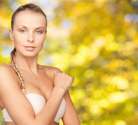 beautiful woman body: beauty, people and body care concept - beautiful young woman with bare shoulders over yellow autumn background